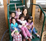 Mara Leong-Nichols, Development Assistant, surrounded by some of the children at Mothers' Club.